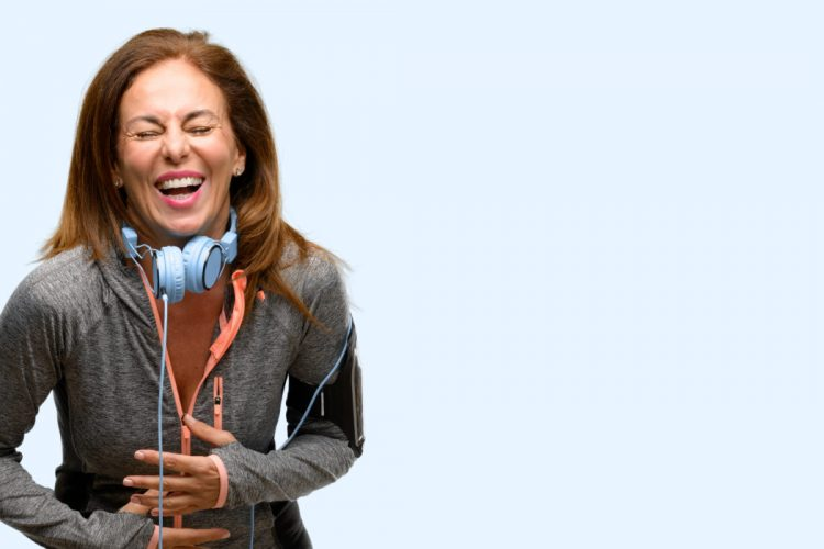 Middle age gym fit woman with workout headphones confident and happy with a big natural smile laughing isolated blue background