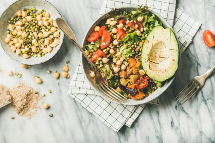 Vegan lunch bowl. Flat-lay of dinner with avocado, grains, beans, sprouts, greens and vegetables over marble background, top view. Clean eating, vegetarian, healthy diet food concept